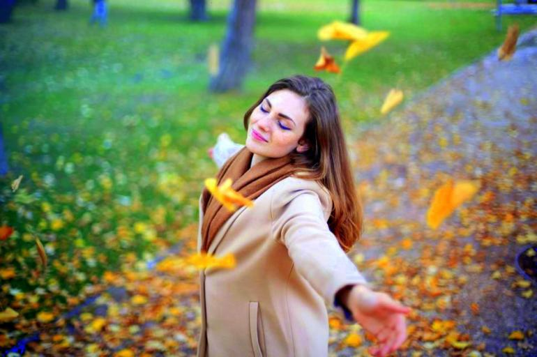 beautiful-young-adult-woman-playing-among-falling-autumn-leaves